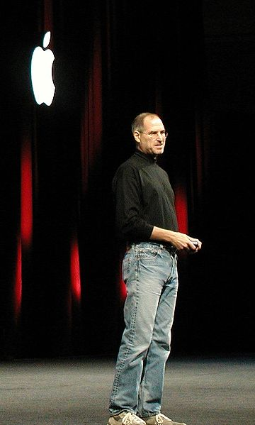 Steve Jobs, wearing his trademark jeans and tennis shoes (and black turtleneck)